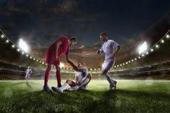 El jugador de fútbol ayuda al onother uno en panorama del fondo del estadio de la puesta del sol Imagenes de archivo