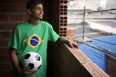 El jugador de fútbol brasileño joven sonriente mira hacia fuera la ventana de Favela Fotografía de archivo libre de regalías