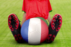 El jugador de fútbol con la bola se sienta en el campo Imágenes de archivo libres de regalías
