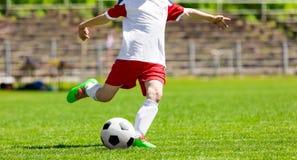 El jugador de fútbol del fútbol de la juventud golpea una bola Futbolista Kicking Ball Imagen de archivo libre de regalías
