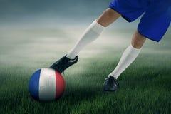 El jugador de fútbol ejercita para golpear una bola con el pie en el campo Imagenes de archivo