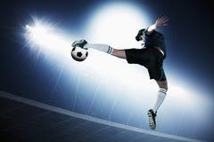 El jugador de fútbol en el mediados de aire que golpea el balón de fútbol con el pie, estadio se enciende en la noche en fondo fotografía de archivo