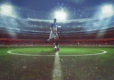 El jugador de fútbol golpea la bola del medio campo en el estadio imágenes de archivo libres de regalías