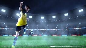 El jugador de fútbol joven está golpeando la bola con el pie mientras que el portero defiende encendido foto de archivo libre de regalías