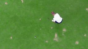 El jugador de golf está golpeando con éxito la bola en una visión superior almacen de video