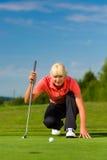 Jugador de golf femenino joven en el curso que apunta para puesto Foto de archivo libre de regalías