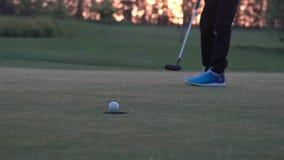 El jugador de golf menor está poniendo de una bola del agujero metrajes