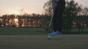 El jugador de golf menor está poniendo de una bola del agujero almacen de video