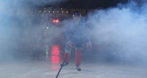 El jugador de hockey profesional con un palillo y un duende malicioso se mueve en Luda en patines y casco en un fondo y un humo o almacen de metraje de vídeo
