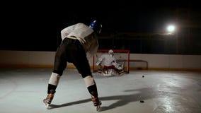 El jugador de hockey profesional produce un tiro en meta en la arena del hielo almacen de metraje de vídeo