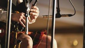 El jugador de la gaita en una falda escocesa toca el instrumento musical en la etapa Imagen de archivo