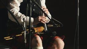 El jugador de la gaita en una falda escocesa toca el instrumento musical en la etapa Foto de archivo