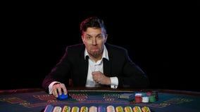 El jugador de póker en línea es feliz sobre ganar en el casino Cierre para arriba metrajes