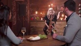 El jugador de saxofón de sexo femenino realiza una canción para un par joven una fecha almacen de video
