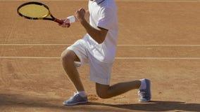 El jugador de tenis acertado en uniforme del blanco vuelve la bola, ganador de la competencia almacen de video