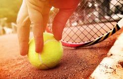 El jugador de tenis consigue la bola Imagen de archivo libre de regalías