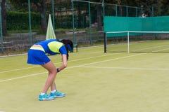 El jugador de tenis de sexo femenino joven dobló abajo para una bola Imágenes de archivo libres de regalías