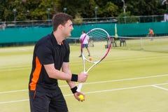 El jugador de tenis de sexo masculino está listo para lanzar la bola Imagen de archivo libre de regalías