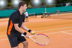 El jugador de tenis de sexo masculino está listo para lanzar la bola en backgrou de la corte de arcilla Imagenes de archivo