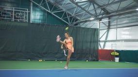 El jugador de tenis hermoso de la muchacha bate profesionalmente la bola y los triunfos almacen de metraje de vídeo