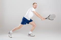El jugador de tenis joven juega a tenis en fondo gris Imagenes de archivo