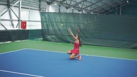 El jugador de tenis de la muchacha golpea la bola con el pie de sus rodillas metrajes