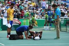 El jugador de tenis profesional Dustin Brown de Alemania necesita la atención médica durante el primer partido de la ronda de la  Imagenes de archivo