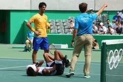 El jugador de tenis profesional Dustin Brown de Alemania necesita la atención médica durante el primer partido de la ronda de la  Imagen de archivo libre de regalías
