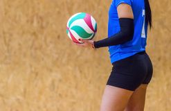 El jugador de voleibol es un jugador de la bola del voleo del atleta de sexo femenino consiguiendo listo para servir la bola imagenes de archivo