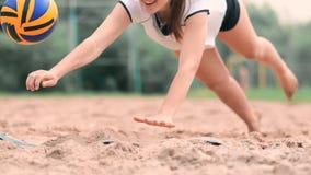 El jugador de voleibol femenino en la caída golpea la bola en la cámara lenta en la playa almacen de video