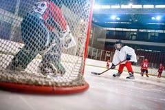 El jugador del hockey sobre hielo tira el duende malicioso en meta foto de archivo