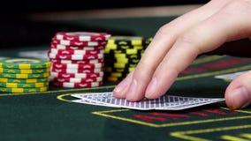 El jugador en el casino controla su póker el jugar de tarjetas, cierre almacen de video