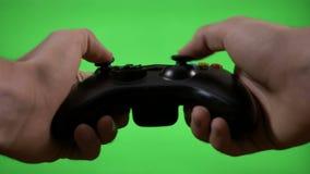 El jugador joven del juego da las llaves de la palanca de mando que controlan que juegan al videojuego en la pantalla verde - almacen de metraje de vídeo
