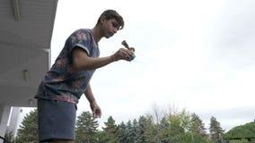 El jugador joven del kendama que ejercita trucos avanzados y los movimientos con kendama juegan afuera en el parque - metrajes
