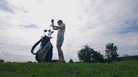 El jugador masculino está eligiendo a un club de golf y se está acostumbrando a él almacen de video