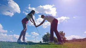 El jugador masculino está enseñando a una señora a golpear la pelota de golf metrajes