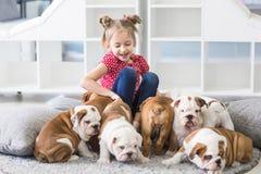 El jugar adolescente de la muchacha con el dogo de los perritos en el piso Foto de archivo