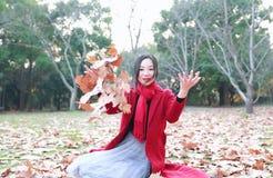 El jugar adolescente de la muchacha con las hojas de otoño para arriba en el aire en parque del otoño Imagenes de archivo