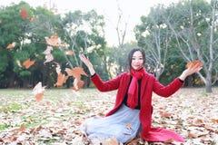 El jugar adolescente de la muchacha con las hojas de otoño para arriba en el aire en parque del otoño Imágenes de archivo libres de regalías