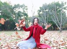 El jugar adolescente de la muchacha con las hojas de otoño para arriba en el aire en parque del otoño Fotografía de archivo libre de regalías