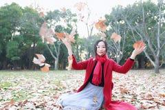 El jugar adolescente de la muchacha con las hojas de otoño para arriba en el aire en parque del otoño Fotos de archivo libres de regalías