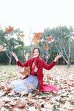 El jugar adolescente de la muchacha con las hojas de otoño para arriba en el aire en parque del otoño Imagen de archivo