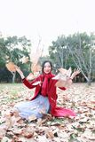 El jugar adolescente de la muchacha con las hojas de otoño para arriba en el aire en parque del otoño Fotos de archivo