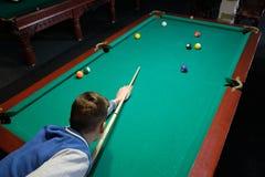 El jugar adolescente en billar americano de la piscina Imagen de archivo libre de regalías