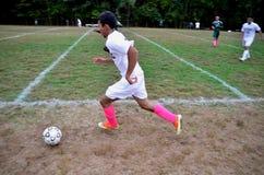 El jugar adolescente en un partido de fútbol de la escuela secundaria imágenes de archivo libres de regalías