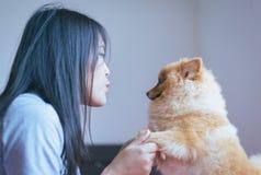 El jugar adolescente joven asiático alegre de la muchacha y diversión feliz con su perro en casa Imagen de archivo libre de regalías
