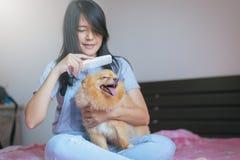 El jugar adolescente joven asiático alegre de la muchacha y diversión feliz con su perro en casa Fotografía de archivo libre de regalías