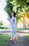 El jugar adolescente joven asiático alegre de la muchacha y diversión feliz con su perro en el parque público Imagen de archivo