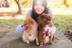 El jugar adolescente joven asiático alegre de la muchacha y diversión feliz con su perro en el parque público Foto de archivo libre de regalías