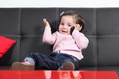 El jugar casual del bebé feliz con un teléfono móvil Imágenes de archivo libres de regalías